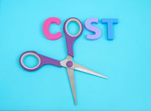 Cost cutter. ' Cost Cutter ' in upper case letters with the 'o' in the word cost replaced by the finger hole of a pair of scissors Royalty Free Stock Photos