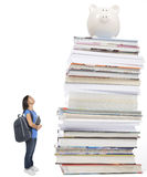 Cost of education. Young student looking up at a pile of books with piggy bank. Concept for high education costs Stock Photography