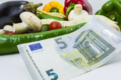 Cost of food. Cost food concept-five euro banknote and vegetables on white background Royalty Free Stock Image