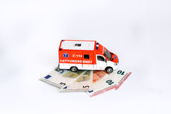 Cost of health care:  Ambulance car with Euro money Royalty Free Stock Images