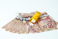 Cost of health care. Canadian dollar bill with syringe and pills Royalty Free Stock Photo
