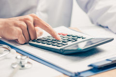 Cost of health care concept, stethoscope and calculator on table Royalty Free Stock Images