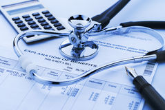 Cost of health care. Figuring cost of health care and benefits with stethoscope and calculator in background Stock Photos