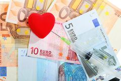 Cost of health care: red heart syringe on euro money Royalty Free Stock Images