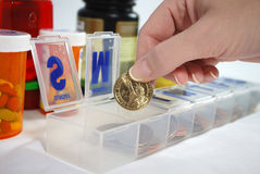 Cost of Healthcare. Open pill box stuffed with American coinage with female hand retrieving a gold American dollar from the box Royalty Free Stock Photos