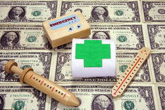 Cost of Healthcare. Childrens toy doctors kit on a sheet on one dollar bills Stock Photo