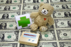Cost of Healthcare. Medical pager and bandage (toy) with teddy bear on sheet of dollar bills Stock Photo