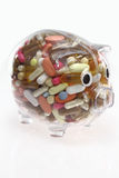 Cost of Healthcare. Piggy bank with pills inside Royalty Free Stock Photography