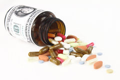 Cost of Healthcare. Pills com out from a medicine bottle Royalty Free Stock Photo