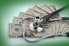 The cost of healthcare. Money and stethoscope to illustrate the cost of health care Royalty Free Stock Images