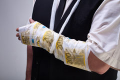 Cost of healthcare concept. With euro banknotes bandage on male hand - closeup Stock Photography