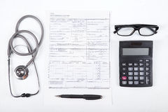 Cost of healthcare concept. Stethoscope, health form, pen, glasses, and calculator Royalty Free Stock Photo