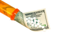 Cost of Healthcare. A perscription bottle with a $100 dollar bill spilling out with white pills Stock Photo