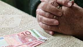 Cost of living of senior sitizens. Hands of senior woman on table with some euro banknotes on stock footage