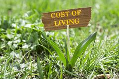 Cost of living. Sign in garden with white spring flower stock photos