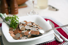 Cost of living with spoonful. A visual depiction of the cost of living using Canadian coins in place of food. here a spoon of money is in the bowl stock photo