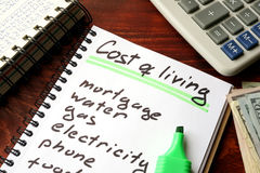 Cost of living written in a notebook. Cost of living written in a notebook and calculations of home finances Royalty Free Stock Image