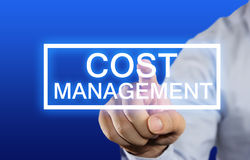 Cost Management. Business concept image of a businessman clicking Cost Management button on virtual screen over blue background Stock Image