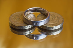 Cost of marriage. Coins and wedding ring, to represent the costs and expenses involved in marriage Royalty Free Stock Photos