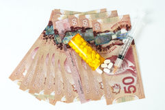 Cost of medicine. Canadian dollar bill with syringe and pills Stock Photo