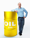Cost of oil. Smiling standing young worker with golden oil barrell isolated on white background stock photos