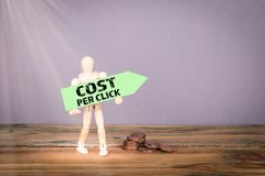 Cost Per Click. Wooden man with green an arrow. Cost Per Click concept. Wooden man with green an arrow royalty free stock photo