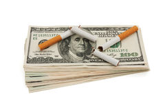 The cost of smoking. A stack of American money with a broken cigarettes on white, The cost of smoking Royalty Free Stock Photo