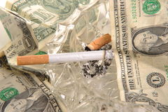 Cost of smoking. Photograph of a cigarette, on a an ashtray with dollar bills Stock Photography