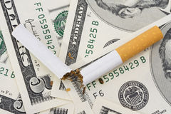 Cost of Smoking. Broken cigarette on American five dollar bills Royalty Free Stock Photos