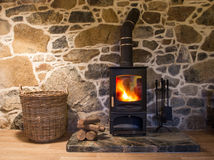 Cosy Stone Cottage Wood Burner. The interior of a stone walled cottage showing the hearth and fireplace with a fire ablaze in a log burning stove, storage basket Royalty Free Stock Images