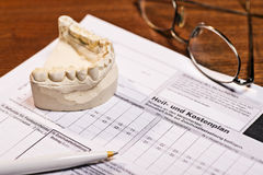 Cost of treatment at the dentist. Plaster cast of teeth and treatment and cost plan by the dentist. The cost plan is labeled with the German word Heil- und Royalty Free Stock Images