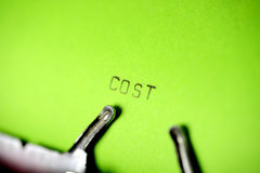 Cost Typing. Cost type on typewriter with green paper background Royalty Free Stock Image