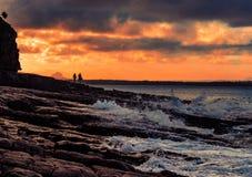 Costa acima do céu colorido do por do sol com surfistas foto de stock royalty free