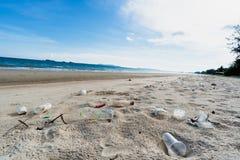 Costa arenosa do mar sujo, poluição ambiental, poluição plástica das garrafas de água no oceano imagem de stock
