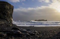 A costa atlântica com areia preta e as rochas enormes da lava imagens de stock