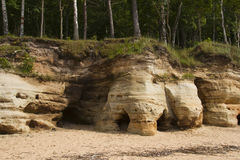 Costa báltica con las rocas de la piedra arenisca y arena blanca cerca de Vidzeme, Letonia Foto de archivo