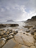 Costa Blanca Beach. Seascape of a rocky beach in the Costa Blanca of Spain, with the mountain of Ifach and the skyline of Calpe on the background Royalty Free Stock Photos