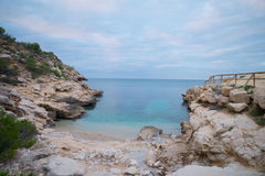 Costa Blanca nudist beach. Conill, one of the most popular nudist beaches on Costa Blanca, Spain, amidst scenic rocky landscape Royalty Free Stock Images