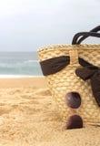 Costa, bolso de la playa de la paja y gafas de sol Foto de archivo