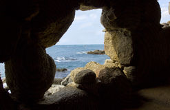 Costa brava beach view through a cave hole Royalty Free Stock Photos