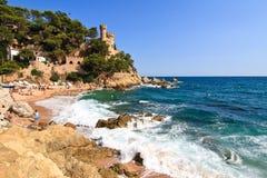 COSTA BRAVA, SPANIEN, 2012: Strand mit Schloss im Hintergrund Stockfotos