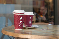 Costa Coffee on Wood Table. Two Costa Coffee Cups on the Wood Table royalty free stock photo