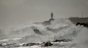 Costa com ondas e o farol fortes Imagem de Stock Royalty Free