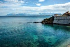 Costa costa con aguas azules cristalinas bajo los cielos azules y wh Fotos de archivo libres de regalías