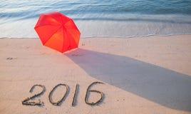 Costa con el paraguas y 2016 exhaustos en la arena Foto de archivo libre de regalías