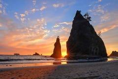 Costa costa con las pilas del mar en la puesta del sol fotos de archivo
