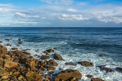 Costa con las rocas, ondas, aguas azules profundas, cielos azules con whi Imagen de archivo