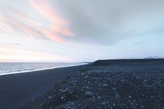costa con las rocas y cielo nublado en la puesta del sol, solheimasandur imagenes de archivo