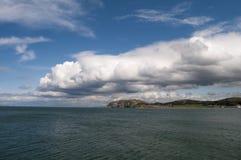 Costa costa con el cielo azul y las nubes Fotos de archivo libres de regalías