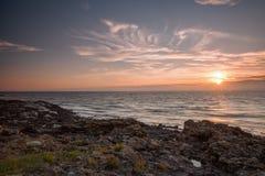 Costa costa de la puesta del sol con los rayos de sol Imágenes de archivo libres de regalías